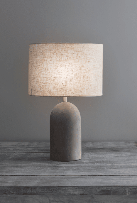 """Concrete Bullet Table Lamp, It's accompanied with a Linen shade, biscuit in colour with specks of brown and grey."""